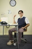 Nerdy Asian man sitting at desk