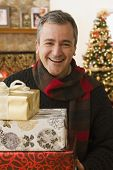 Caucasian man holding Christmas gifts