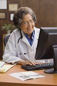 Senior Hispanic female doctor using computer at desk