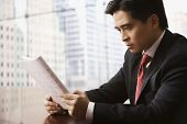 Chinese businessman reading report