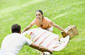 Hispanic couple laying out picnic blanket