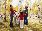 African family holding hands around tree