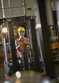 Hispanic warehouse worker driving forklift