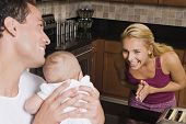 Hispanic mother smiling at baby