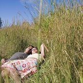 Indian couple laying in tall grass