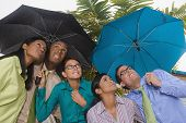 Hispanic businesspeople standing under umbrellas