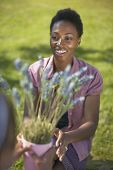 African woman reaching for potted plant