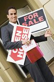 Hispanic real estate agent holding signs