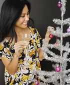 foto of pacific islander ethnicity  - Pacific Islander woman decorating Christmas tree - JPG