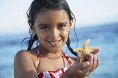 Hispanic girl holding starfish