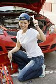 Asian woman fixing car