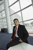 Hispanic businessman sitting on edge of table