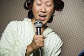 Asian woman in curlers singing