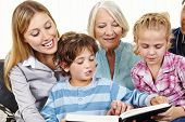 Happy family in three generations reading a book in the living room