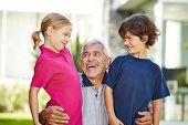 Happy grandfather with two grandchildren together in a garden