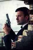 Постер, плакат: Hitman in tuxedo holding a gun