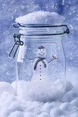 Snowman in glass jar with snowfall - blue tone effect added