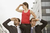 Hispanic businesswoman sitting on co-worker's shoulders