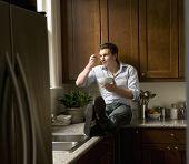 Hispanic man eating on kitchen counter