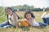 picture of chums  - Hispanic sister sitting next to pumpkin - JPG