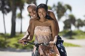 Multi-ethnic couple sitting on bicycle