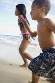 Pacific Islander siblings running on beach