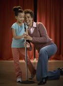 African mother and daughter singing in microphone