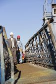 Multi-ethnic businessman and construction worker walking