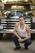 Hispanic man with tattoos in front of truck