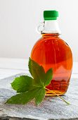 Maple Syrup In A Bottle On Stone Plate