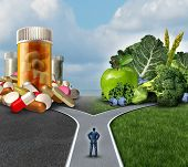 stock photo of antibiotics  - Medication decision concept and natural remedy nutrition choices dilemma between healthy fresh fruit and vegetables or pharmaceutical pills and prescription drugs with a man on a crossroad trying to decide the best path to health - JPG