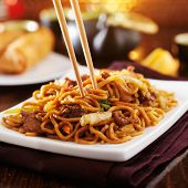 stock photo of lo mein  - eating chinese beef lo mein with chopsticks - JPG