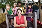 image of playgroup  - Diverse group of preschool 5 year old children playing in daycare with teacher - JPG
