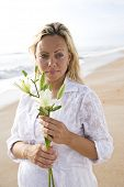 foto of sand lilies  - Young pretty pregnant woman wearing white on beach holding flower - JPG