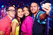 Young people taking selfie at nightclub
