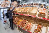 Samara, Russia - October 5, 2014: Young Woman Choosing Fresh Bakery Products At Shopping In Supermar