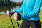 Nordic walking exercise adventure hiking concept - closeup of woman's hand holding nordic walking poles