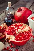 Pomegranate And Bottles Of Essence Or Tincture On Table