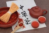 Safflower herb tea with terracotta teapot and cups and calligraphy script on rice paper. Translation