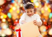holidays, presents, christmas, childhood and people concept - smiling little girl with gift box over red lights background