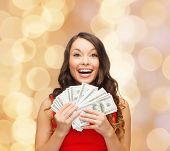 christmas, sale, banking, winning and holidays concept - smiling woman in red dress with us dollar money over beige lights background
