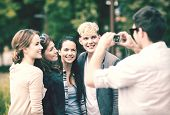 summer holidays and teenage concept - group of teenagers taking photo outside