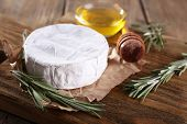Camembert cheese on paper and honey in glass bowl on cutting board on wooden background