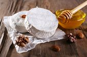 Camembert cheese on paper, nuts and honey in glass bowl on wooden background