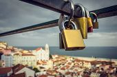 Group of love padlocks attached to a fence over beautiful Lisbon view