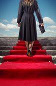 Elegant woman in black coat climbing a red carpet stairway