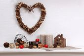 Romantic still life with wicker heart and design details on shelf and white wall background