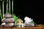 Beautiful composition with spa stones and candle on table on dark background