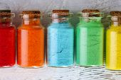 stock photo of pigment  - Bottles with colorful dry pigments on wooden background - JPG