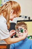 Optometry concept. female doctor ophthalmologist or optometrist helps young boy with phoropter during sight testing or eye examinations in clinic